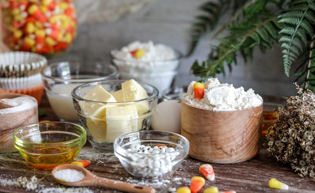 ingredients for gluten free halloween cupcakes, including candy corn, butter, flour