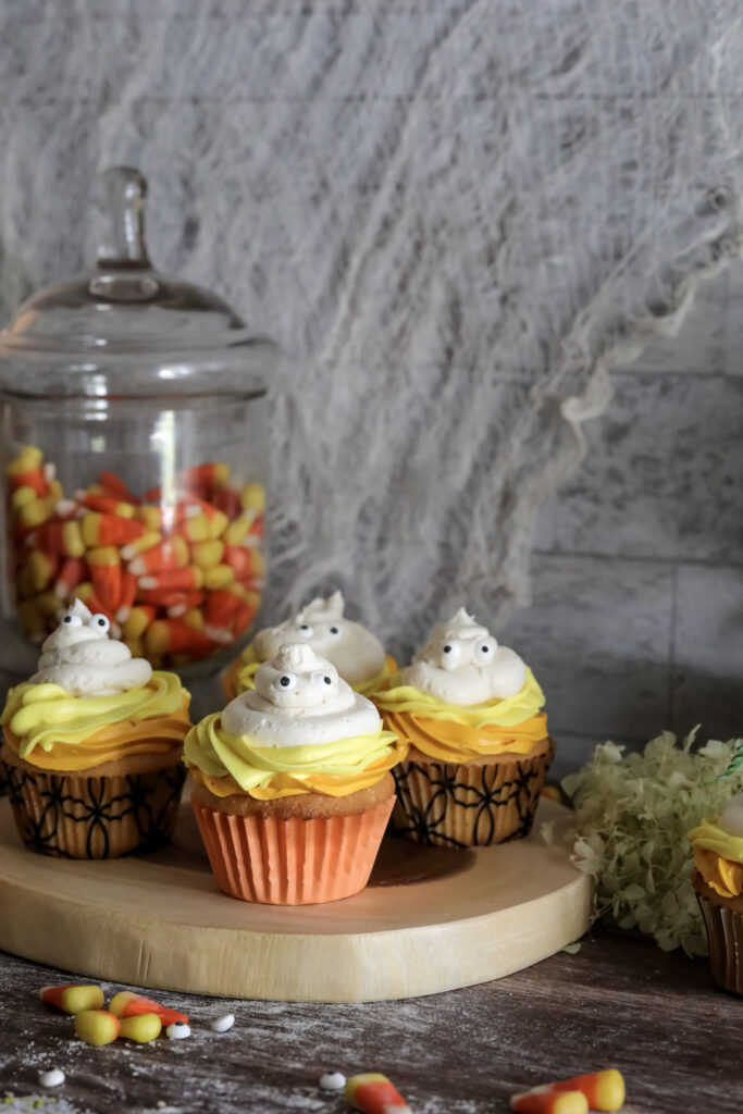 Four Halloween Candy Corn Ghost Cupcakes on a wood serving plater. With candy corns around it.