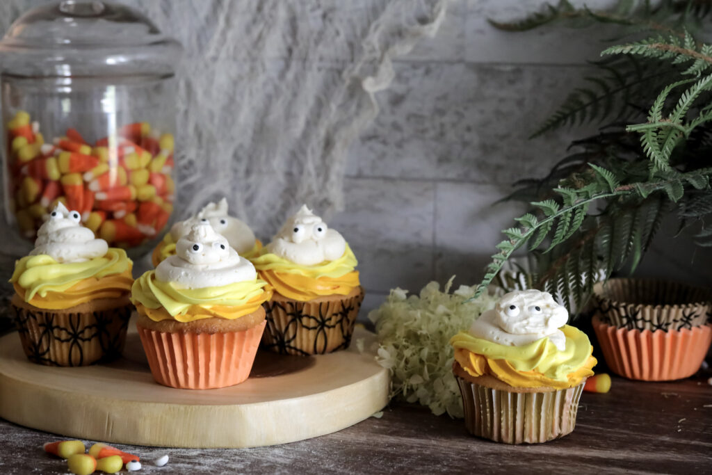 gluten-free halloween cupcakes on a wood plater sitting on a wood table with a jar of candy corn in the background