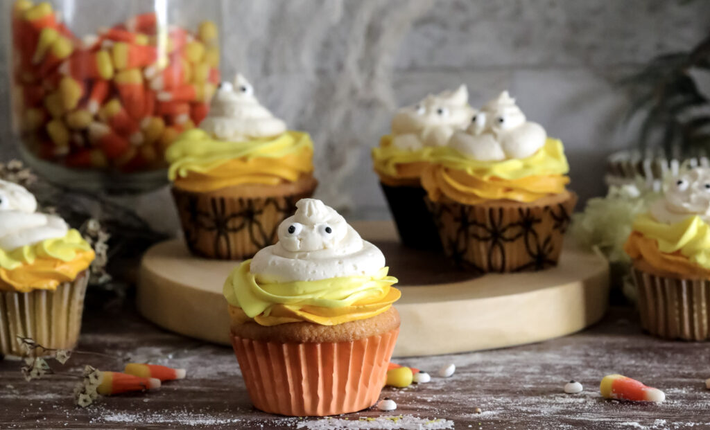 horizonal photo 7 Candy Corn Ghost Cupcakes on a wood serving plater. With candy corns around it.
