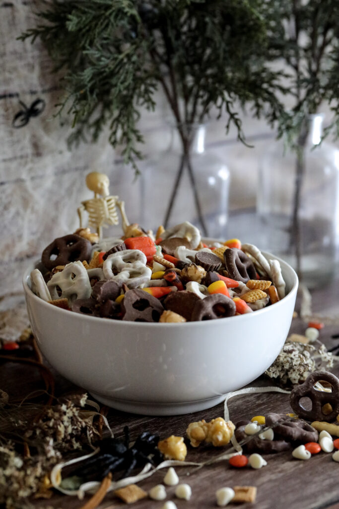 halloween trail mix in a white bowl with a Skelton in the background