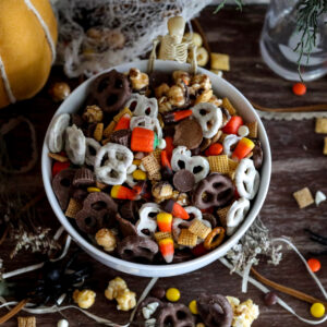 halloween trail mix in a white bowl above photo